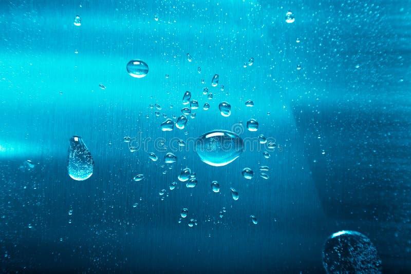 Droppar av vatten på en färgbakgrund grått grunt djupfält Selektivt fokusera blurriness royaltyfri foto