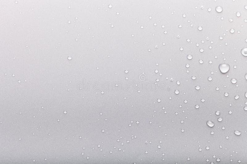 Droppar av vatten p? en f?rgbakgrund gr?tt arkivfoton