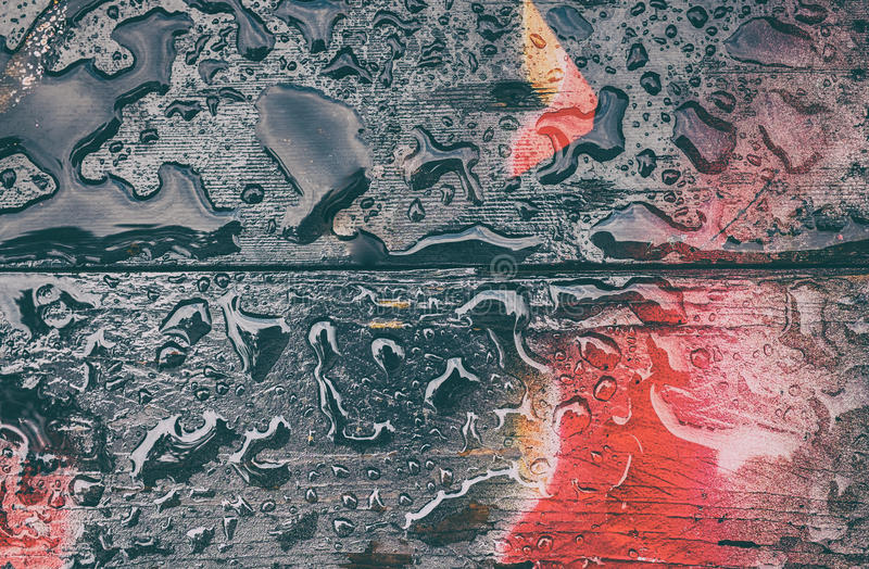 Droppar av vatten som sätta sig på ett trägolv, målas arkivfoto