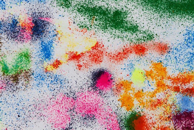 Droppar och teckningar färgade färgpulver på en vit bakgrund arkivfoton