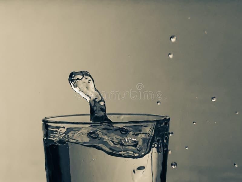Droppe av vatten i bl? bakgrund arkivbilder