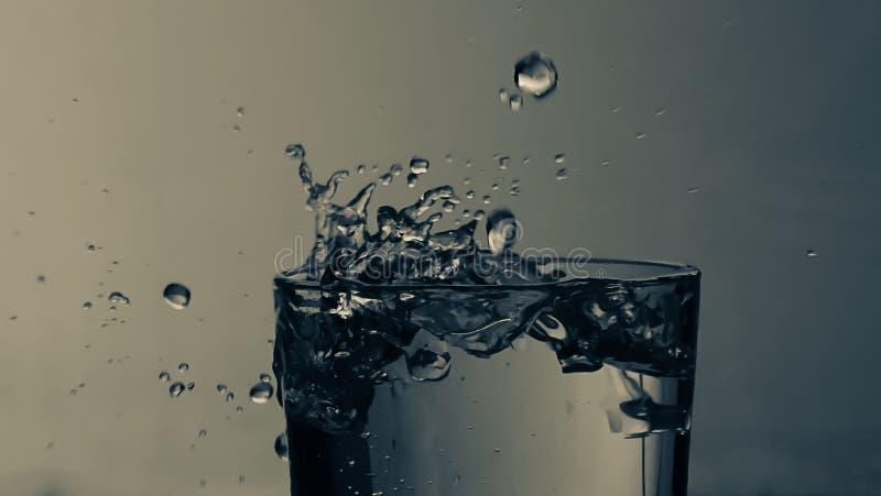 Droppe av vatten i bl? bakgrund arkivbild