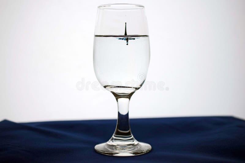 Droppe i ett exponeringsglas av vatten arkivfoton