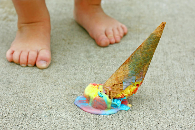 Dropped Ice Cream Cone by Child's Feet royalty free stock image