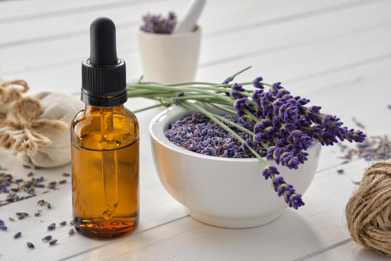 Dropper bottle of essential lavender oil, mortar of dry lavender flowers and sachets on white table royalty free stock photos