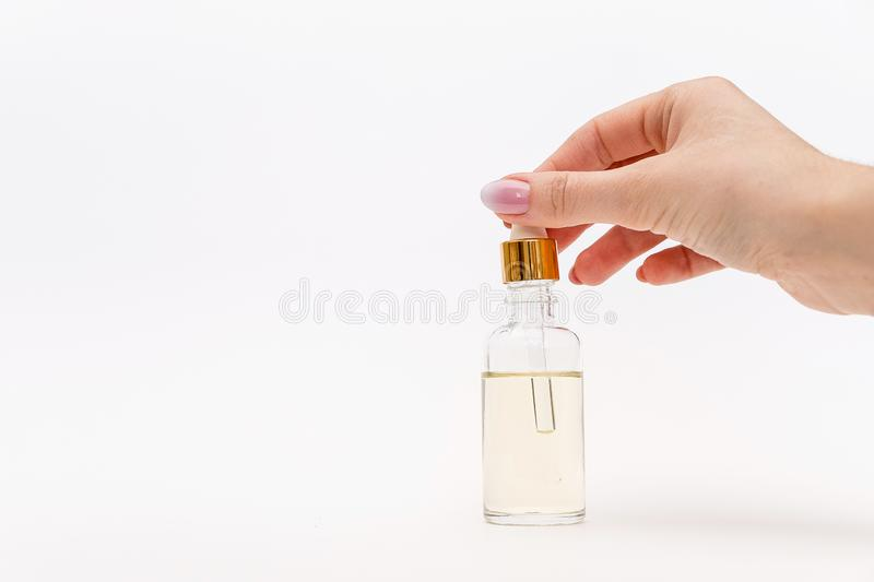 Dropper glass Bottle Mock-Up. Oily drop falls from cosmetic pipette on white background stock images