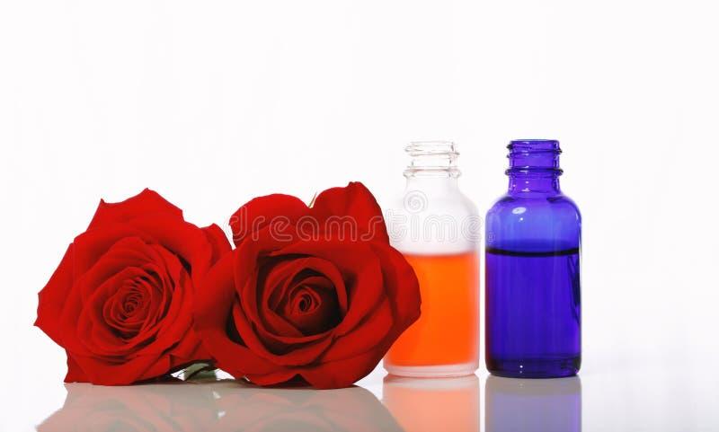 Droppglassflaskor med rosor royaltyfri bild