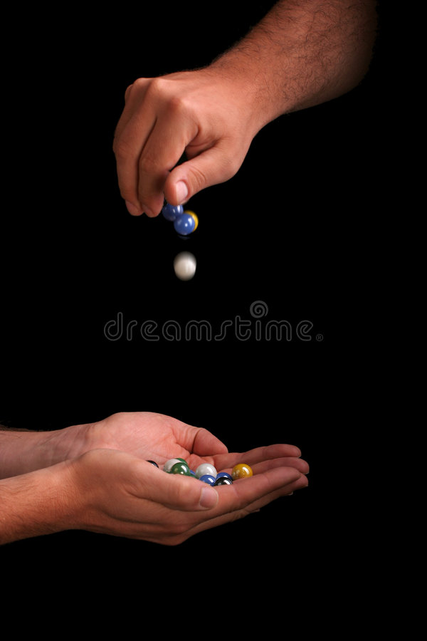 Dropping and catching marbles royalty free stock photos