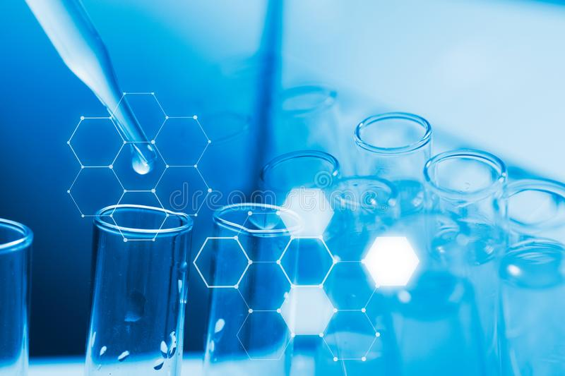 Dropping chemical liquid to test tube, laboratory research and development concept stock photo