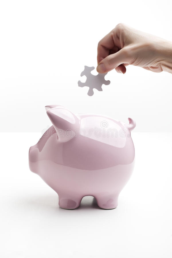Dropping A Puzzle Piece Into Piggy Bank Stock Photography