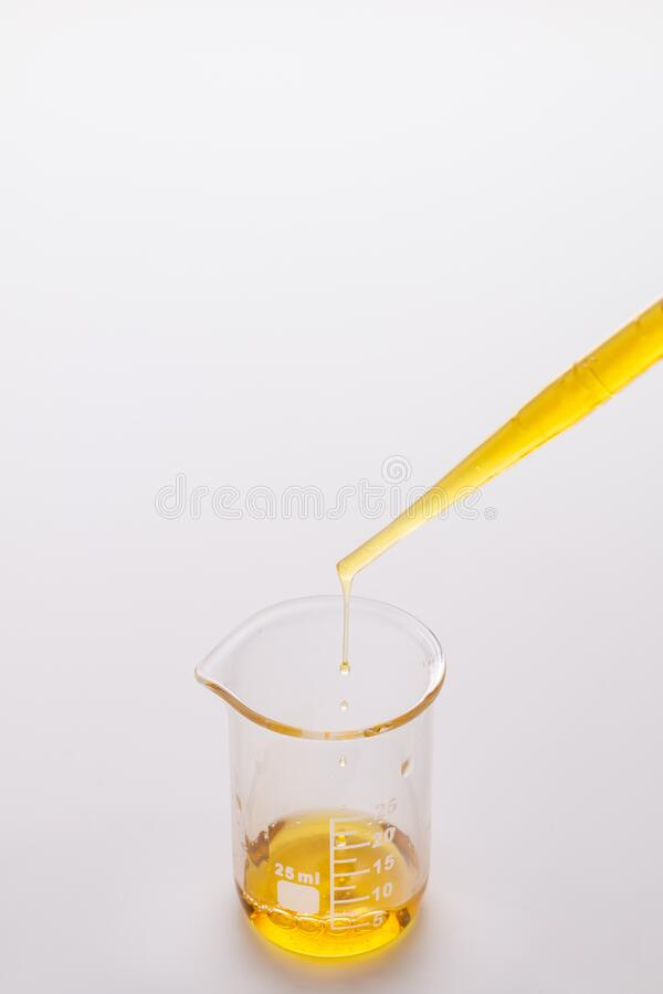 Dropping oil from a pipette into a test beaker royalty free stock photos