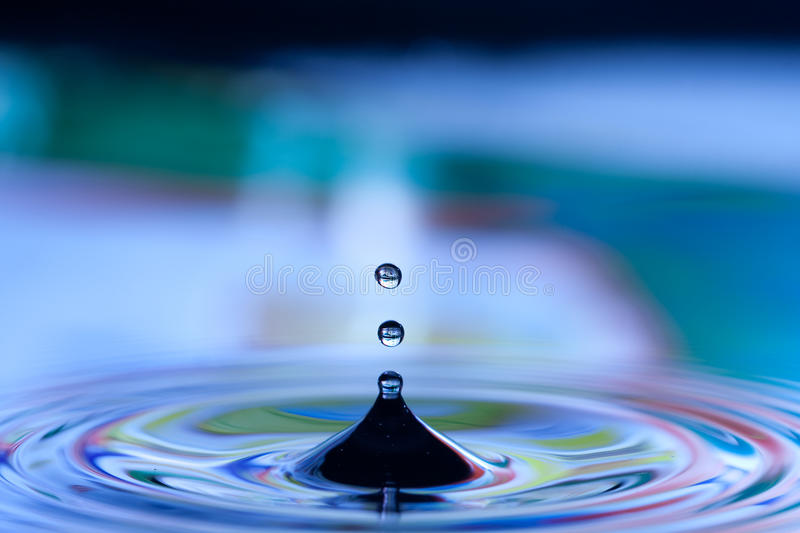 Drops in blue water. Closeup details of drops splashing and causing ripples in blue water stock photo