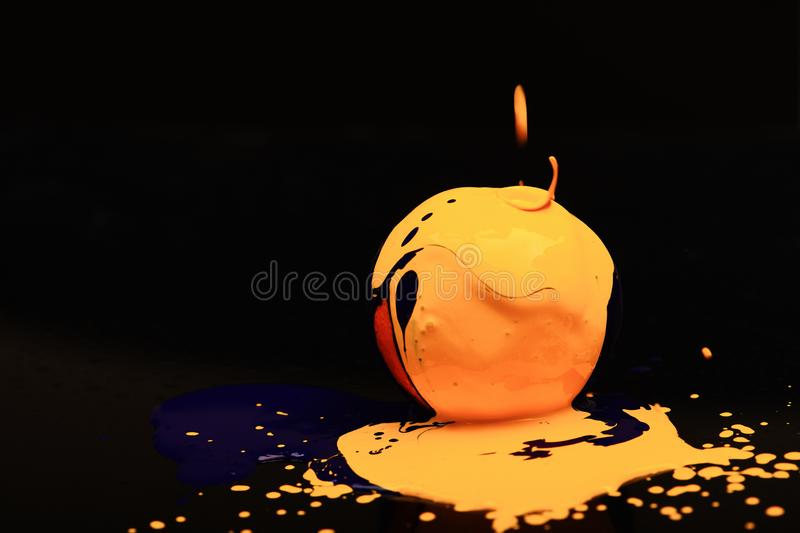 Drops of blue and yellow oil or acrylic paint. Poured on fruit on black background. Orange or grapefruit covered with paints. Paint splashing on orange fruit royalty free stock images