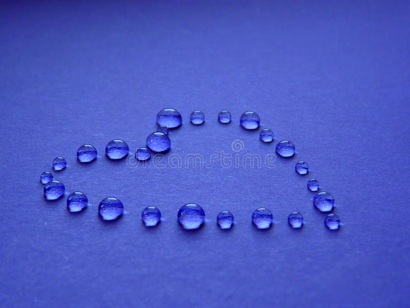 Drops in the form of heart on a blue background stock photography