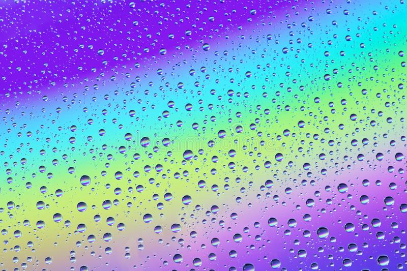 Drops on the glass against the background of the rainbow, texture and background stock photography