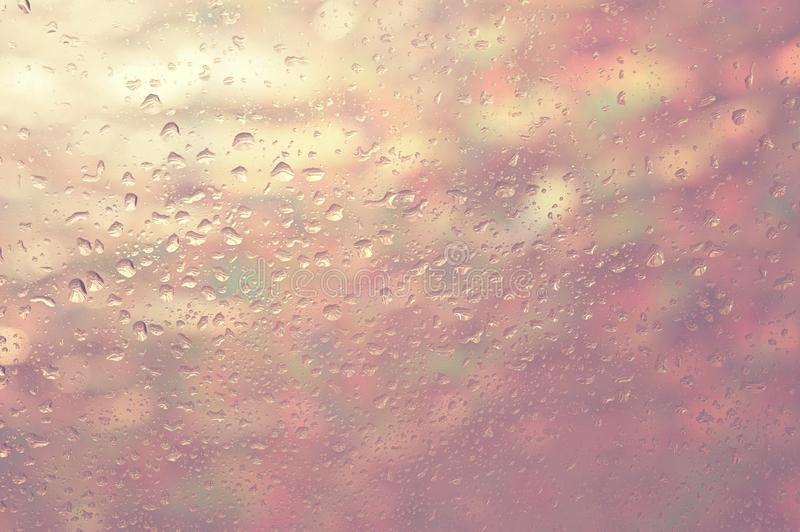Background in pastel colors. Drops on the glass, behind the glass multicolored blurred lights royalty free stock photography