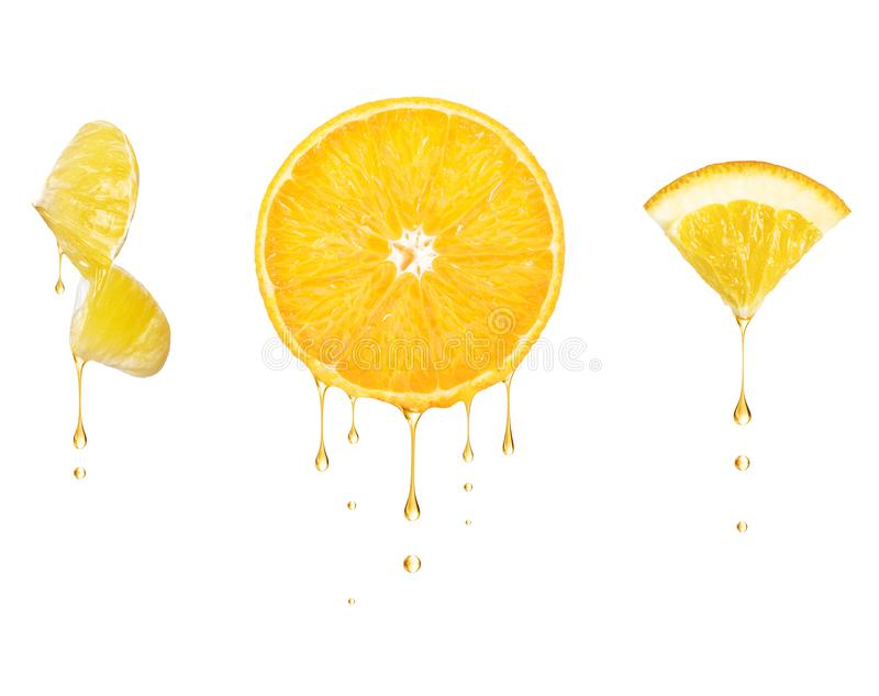 Drops of juice drip from cut pieces of orange, isolated on white background.  stock photo