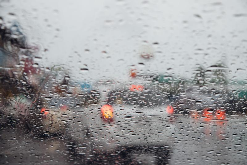 Drops Of Rain Drizzle on the glass windshield in the evening. street in the heavy rain. Bokeh Tail light and Traffic lights in cit. Y. Please drive  car stock images