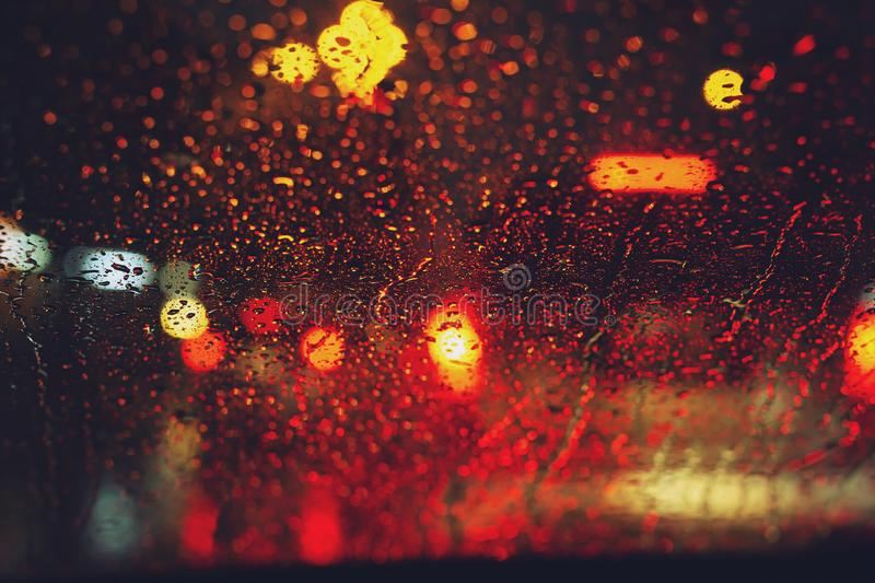 Drops Of Rain Drizzle on the glass windshield in the night. street in the heavy rain. Bokeh Tail light. soft Focus. Please drive carefully, slippery road. soft stock images