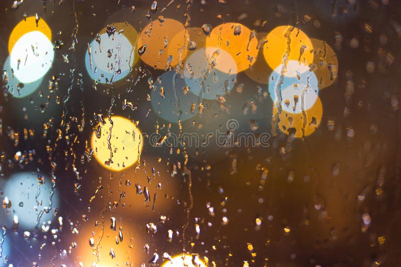 Drops of rain on window, night. Blurred light stock images