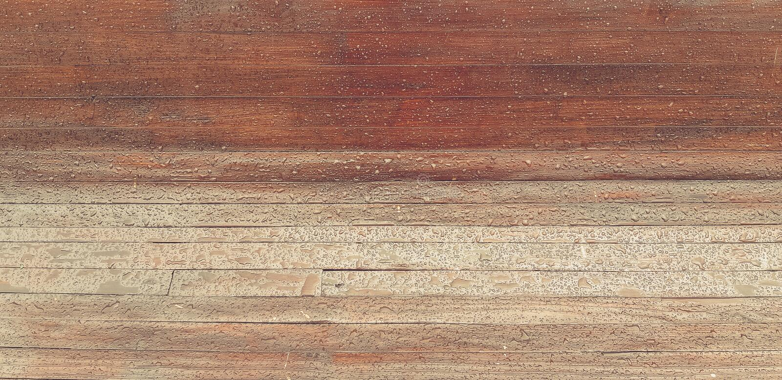 Drops of rain on wooden background. wet bench royalty free stock image
