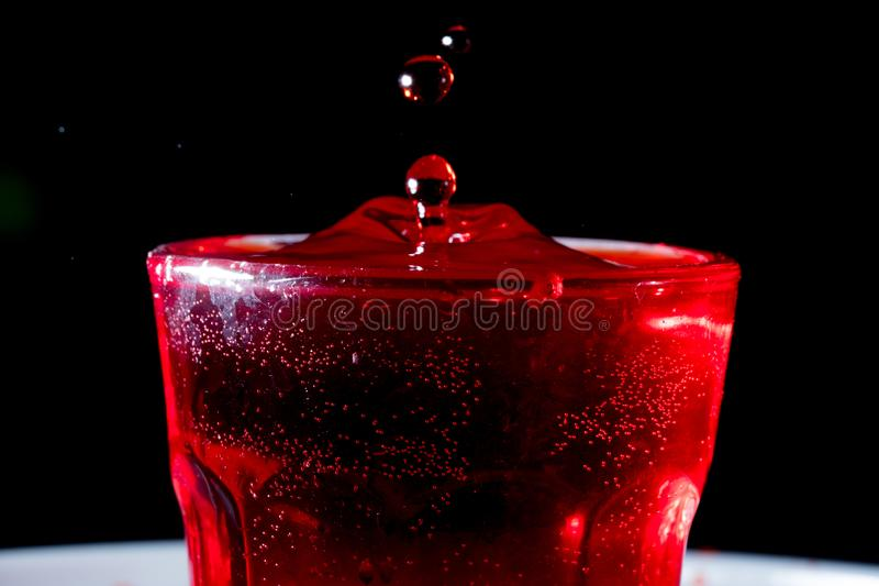 Drops of red liquid. In glass beaker, abstract, alchemy, alcohol, assets, backdrop, background, banner, bar, beautiful, beauty, berry, beverage, blob, blood royalty free stock image