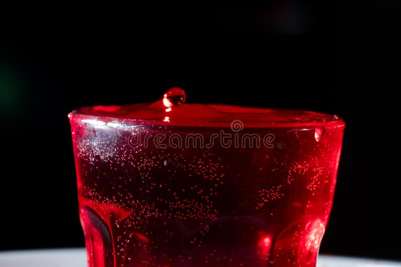 Drops of red liquid. In glass beaker, abstract, alchemy, alcohol, assets, backdrop, background, banner, bar, beautiful, beauty, berry, beverage, blob, blood royalty free stock photography