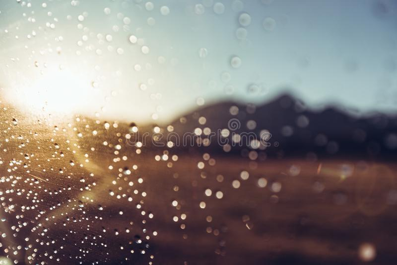 Raindrops On Car`s Wind Shield On The Mountains And Sun, Selective Focus. Travel Journey Concept. Drops of water on the car glass against the background of the royalty free stock photos