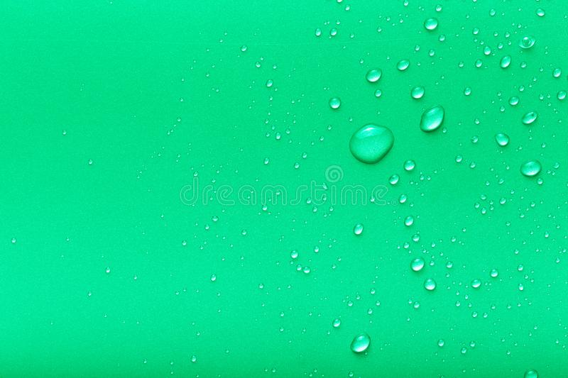 Drops of water on a color background. Green. Toned stock photo