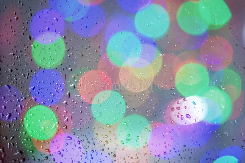 Drops water on a glass surface with blurred colorful bokeh stock image
