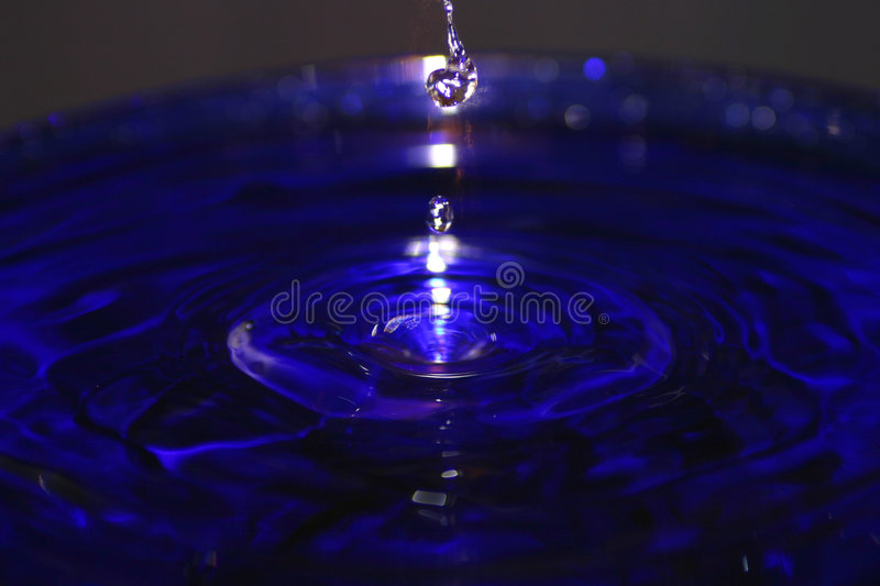 Drops of Water Splashing in a Blue Pool royalty free stock photography