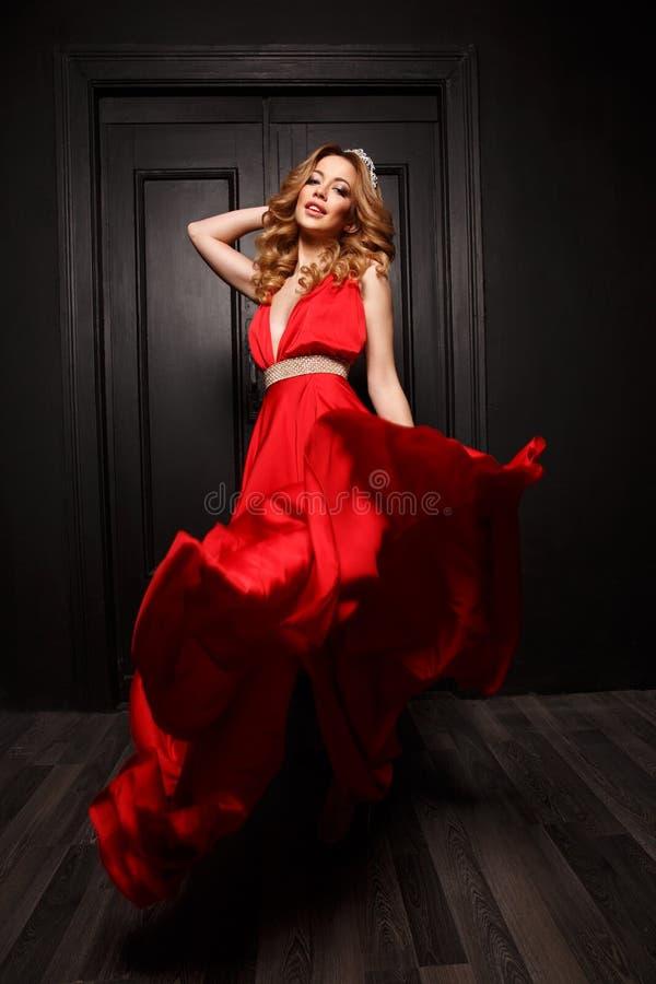 Drottningen av bollen med diademen på hennes huvud är mycket passionerad och bedöva i den eleganta röda aftonen som fladdrar klän royaltyfri fotografi