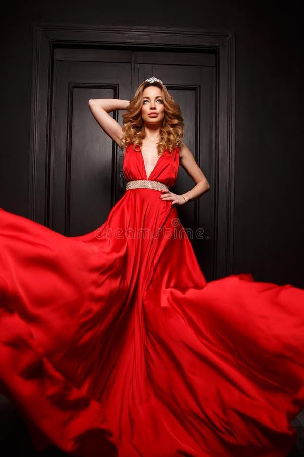 Drottningen av bollen med tiaran på hennes huvud är mycket sexig och charma i den eleganta röda aftonen som fladdrar klänningen royaltyfri bild