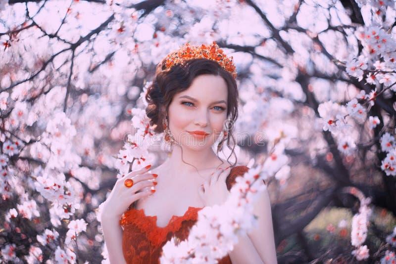 Drottningen av v?ren g?r i den blommande tr?dg?rden, ett st?endefoto av en n?tt kvinna med m?rkt h?r och en guld- krona p? royaltyfri fotografi