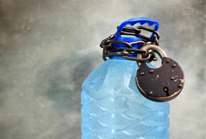 Drought and water scarcity concept with plastic bottle with fresh water, chain and lock. Great value of water idea. royalty free stock images