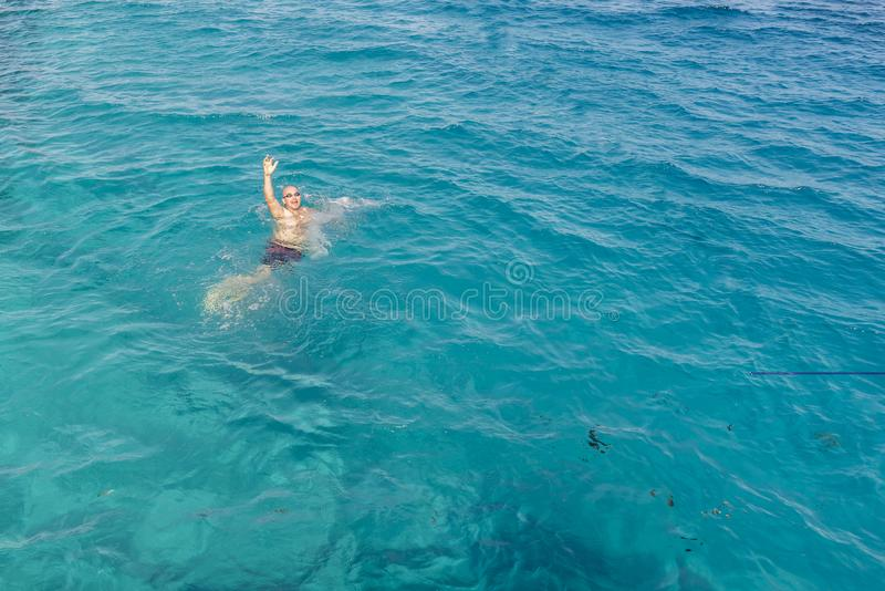 Drowning man in sea asking for help with raised arms. The man is drowning in the sea. man drowning in the sea and waving hand for royalty free stock images