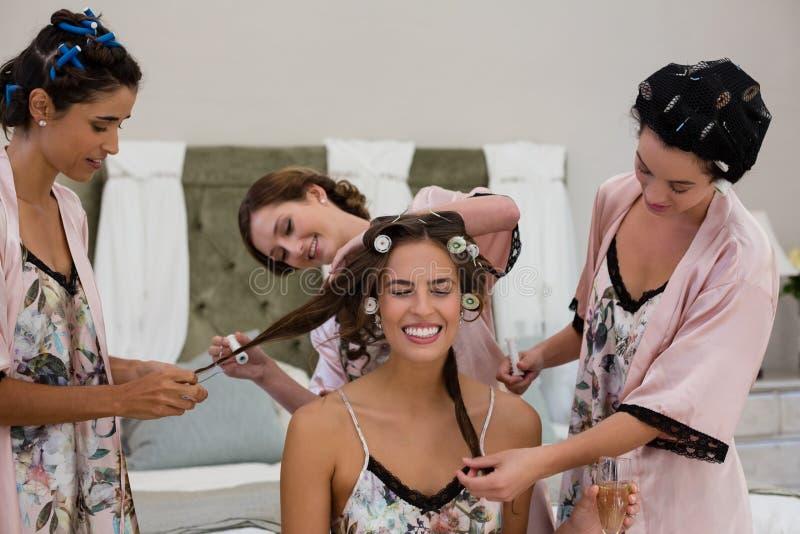Drużka pomaga panny młodej w dostawać przygotowywający fotografia stock