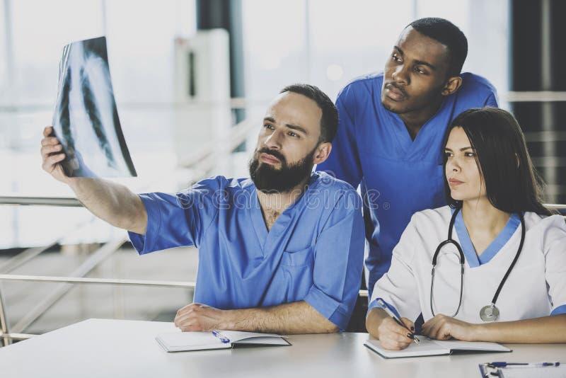 Drużyna lekarki Egzamininuje Radiologicznego obraz cyfrowego W szpitalu obrazy stock