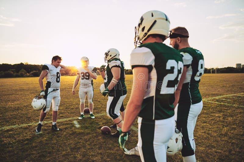Drużyna młodzi futbol amerykański gracze opowiada wpólnie po p zdjęcia royalty free