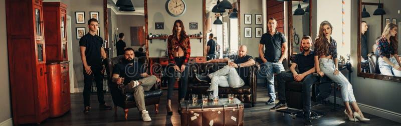 Drużyna od siedem fryzjerów męskich w nowożytnym zakładzie fryzjerskim obraz royalty free