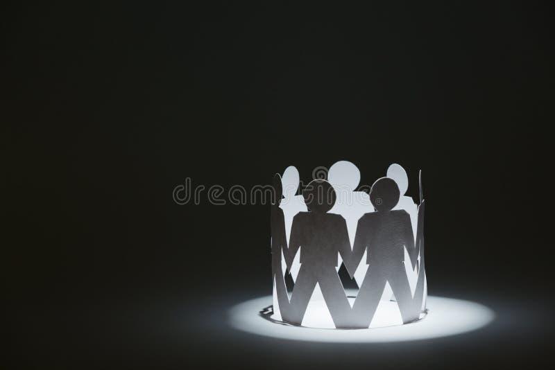 Drużyna papierowi lal ludzie trzyma ręki w świetle fotografia stock