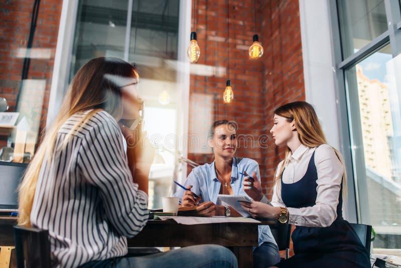 Drużyna pisze puszkowi pomysłach w oficce siedzi przy stołem trzy bizneswomanów młody myśleć nowy biznesowy projekt zdjęcia royalty free