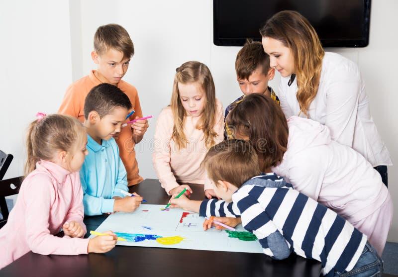 Drużyna podstawowy pełnoletni dzieci rysować zdjęcia stock