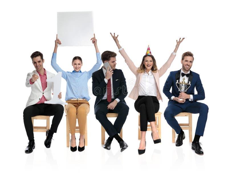 Drużyna posadzeni młodzi ludzie ma zabawę wpólnie obraz royalty free