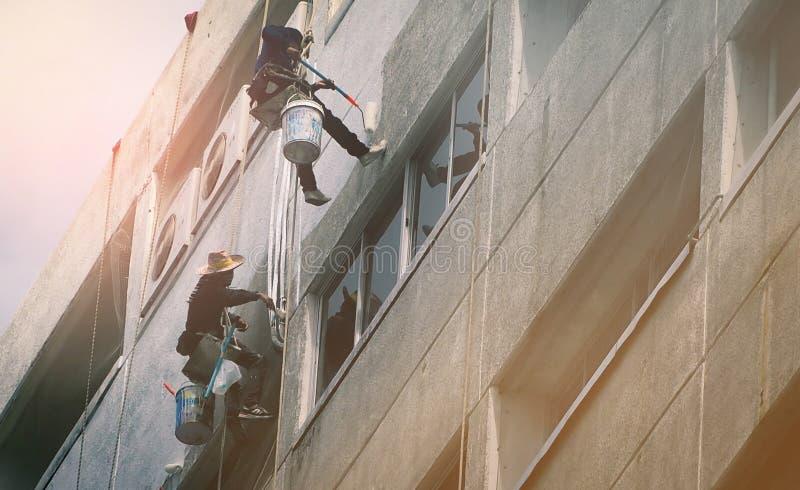 Drużyna pracownicy maluje ściennego wysokiego wzrosta budynek Malarzi malują zewnętrznego budynek biurowego z rolownikiem Niebezp zdjęcia royalty free