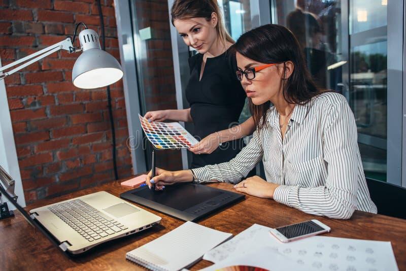 Drużyna rysuje nowego projekt żeński projektant wnętrz używać graficznej pastylki, laptopu i kolor palety obsiadanie, przy biurki zdjęcia stock
