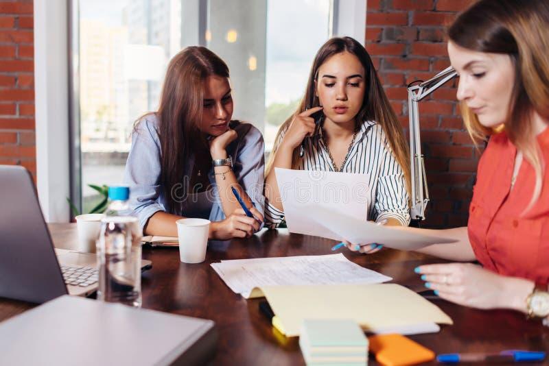 Drużyna studiuje dokumenty pracuje w biurze trzy poważnego żeńskiego kolegi patrzeje, czytający, zdjęcie royalty free