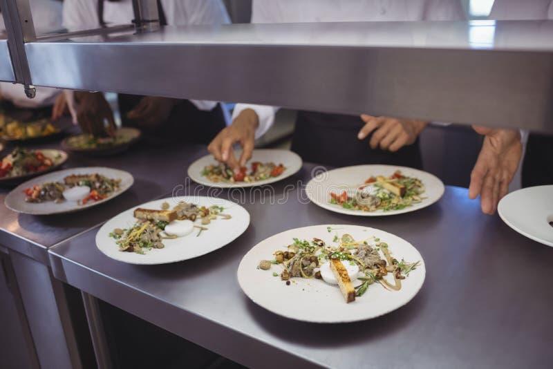 Drużyna szefowie kuchni garniruje posiłek na kontuarze fotografia royalty free