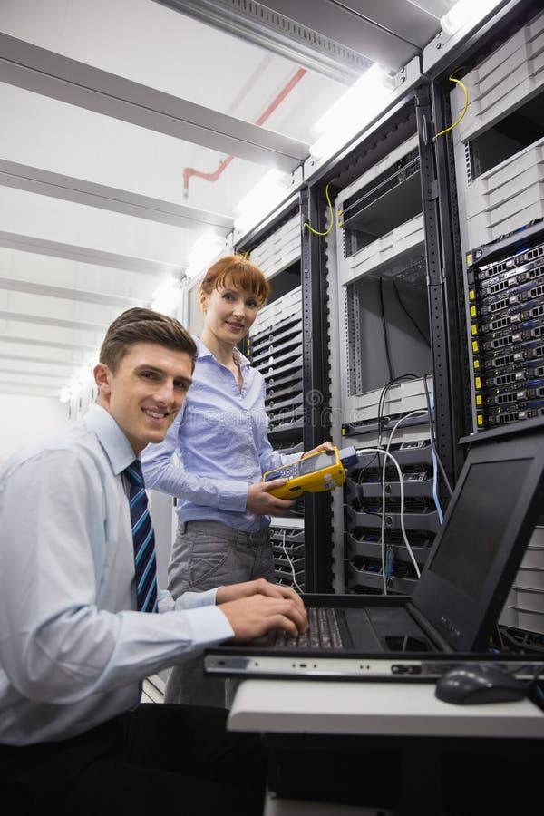 Drużyna technicy używa cyfrowego kablowego analizatora na serwerach fotografia royalty free