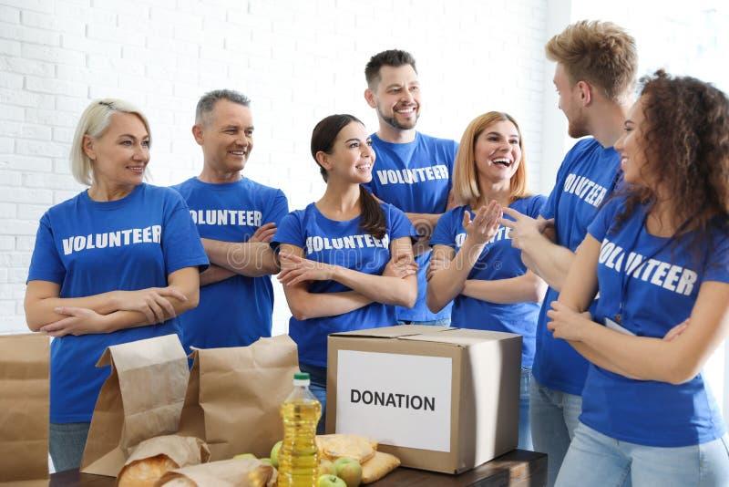 Drużyna wolontariuszi blisko zgłasza z karmowymi darowiznami zdjęcie royalty free